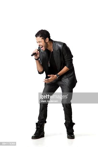 Man standing in studio singing into microphone