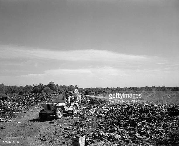 Man standing in the back of a jeep spraying a flybreeding city dump in Edinburg Texas 1946 Flies can transmit foodborne diseases such as cholera...