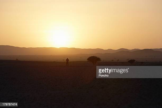 Man standing in the desert watching sunset