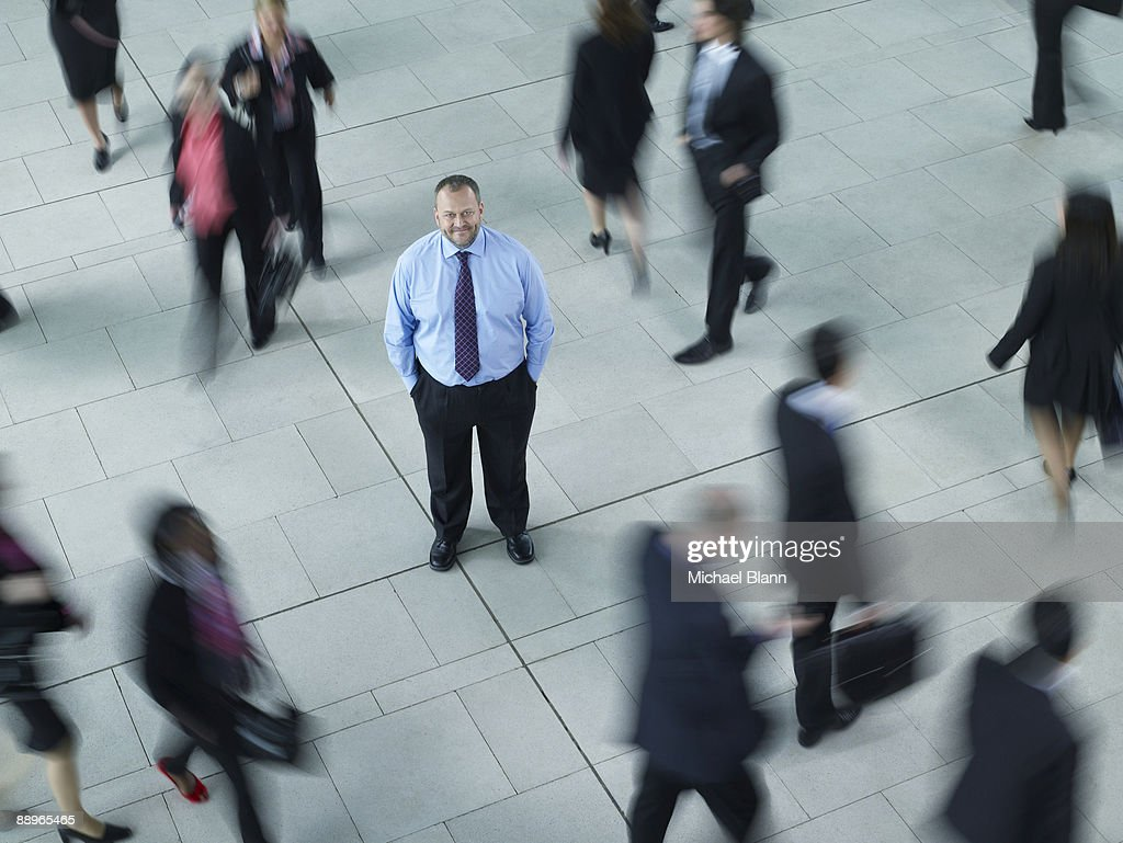 man standing in the middle of a busy crowd : Stock Photo