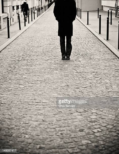 A man standing in the middle of a cobblestone street in Paris, France.