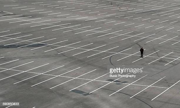 A man standing in the middle of a parking lot