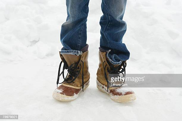Man standing in unlaced snowboots in snow, low section