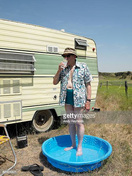 man standing in wading pool, drinking