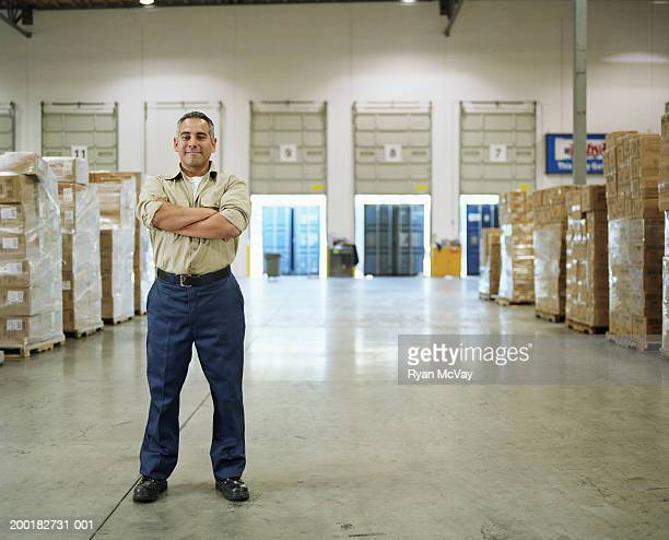 Man standing in warehouse with arms crossed, portrait