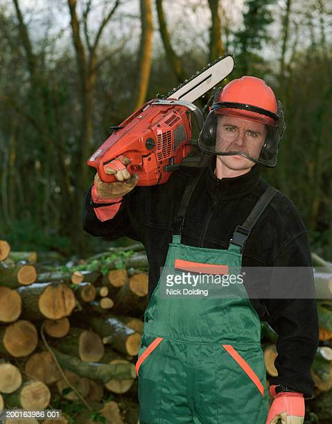 Man standing in woods, holding chainsaw, portrait