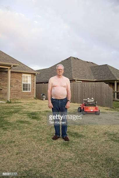 Man standing in yard, shirtless