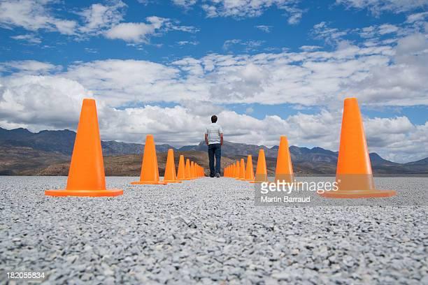 Homem de pé entre duas linhas de cones de segurança
