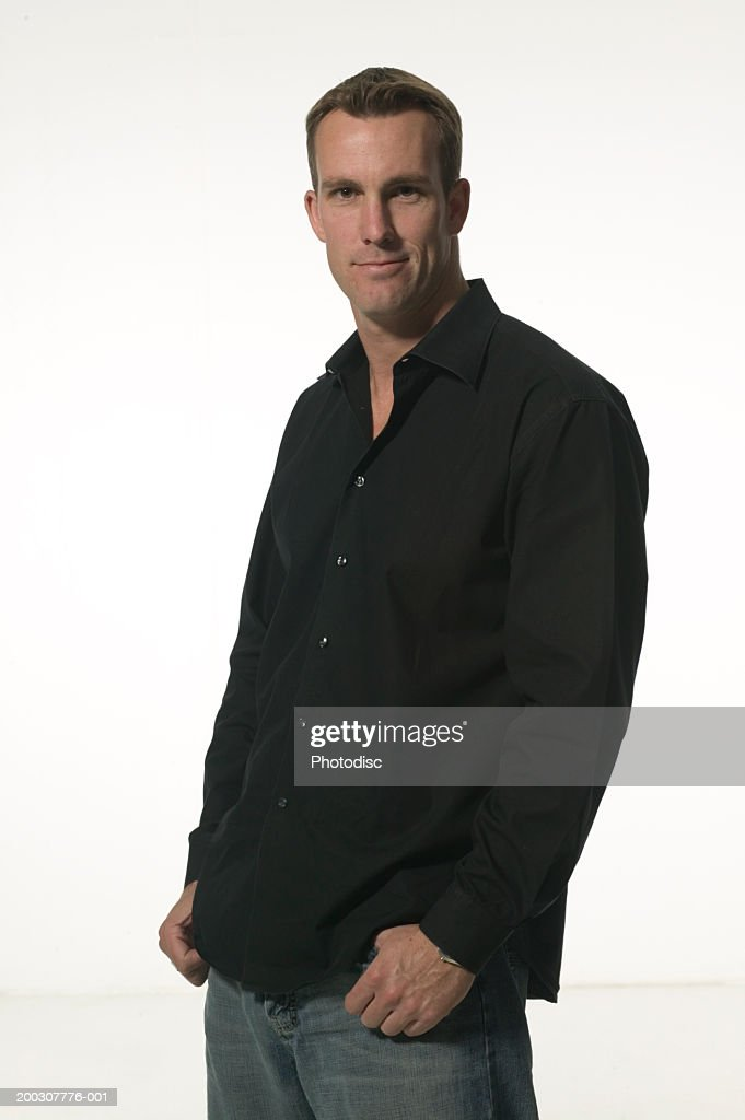 Man standing indoors with hands in pockets, posing, portrait : Stock Photo