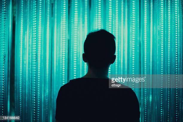 Man standing infront of neon lights