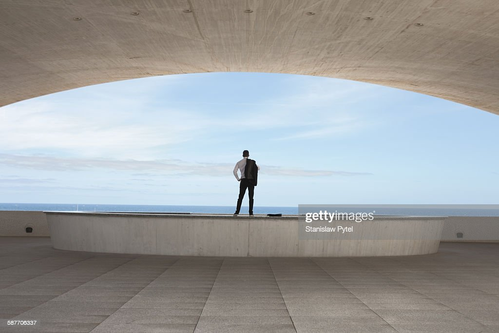 Man standing inside a building looking at ocean