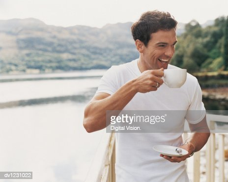 Man Standing Laughing as he Drinks From a Coffee Cup on a Balcony Beside a Lake : Stock Photo