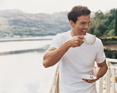 Man Standing Laughing as he Drinks From a Coffee Cup on a Balcony Beside a Lake