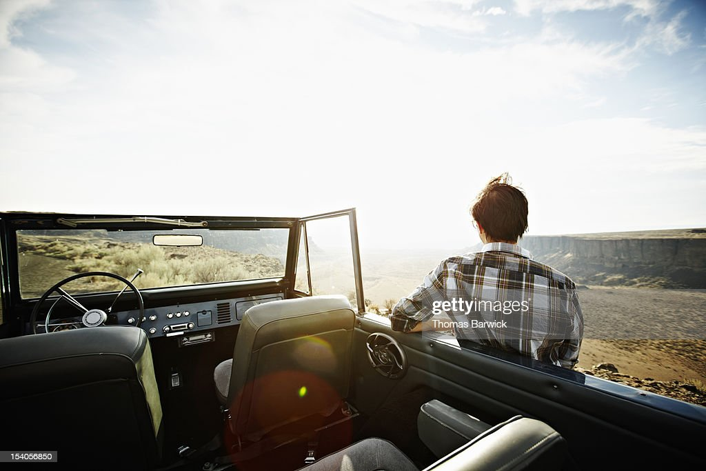 Man standing leaning against side of convertible : Stock Photo