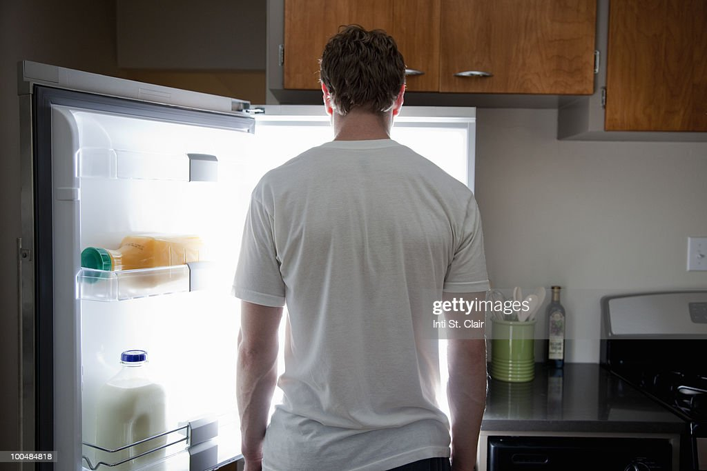 Man standing looking at contents of fridge : Stock Photo
