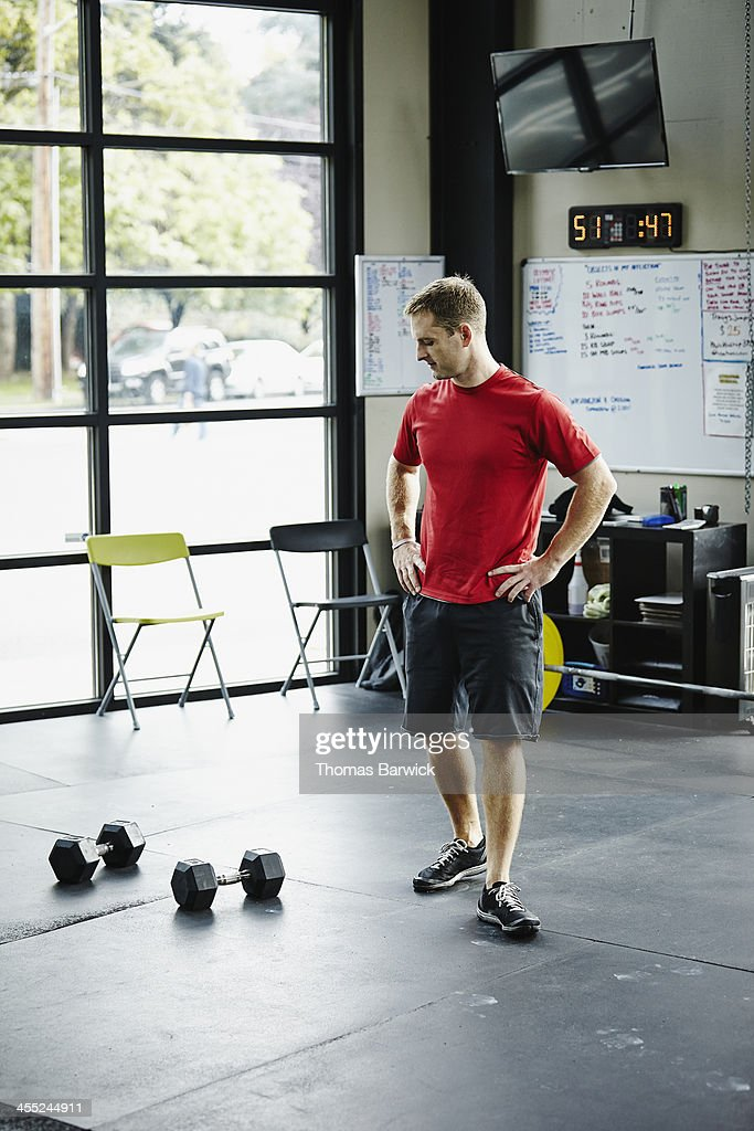 Man standing looking at dumbbells on floor in gym : Stock Photo