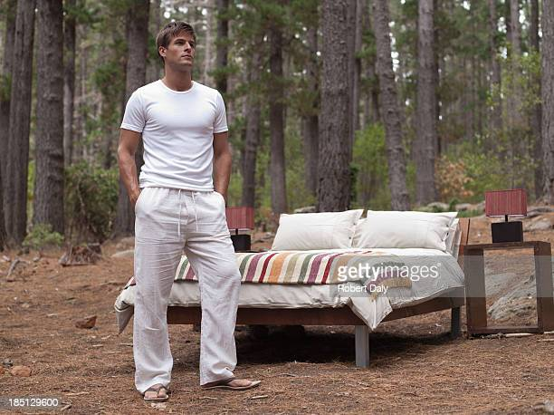 A man standing near bed outdoors in the woods