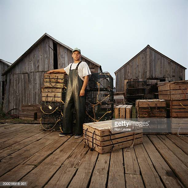 Man standing near lobster crates on dock