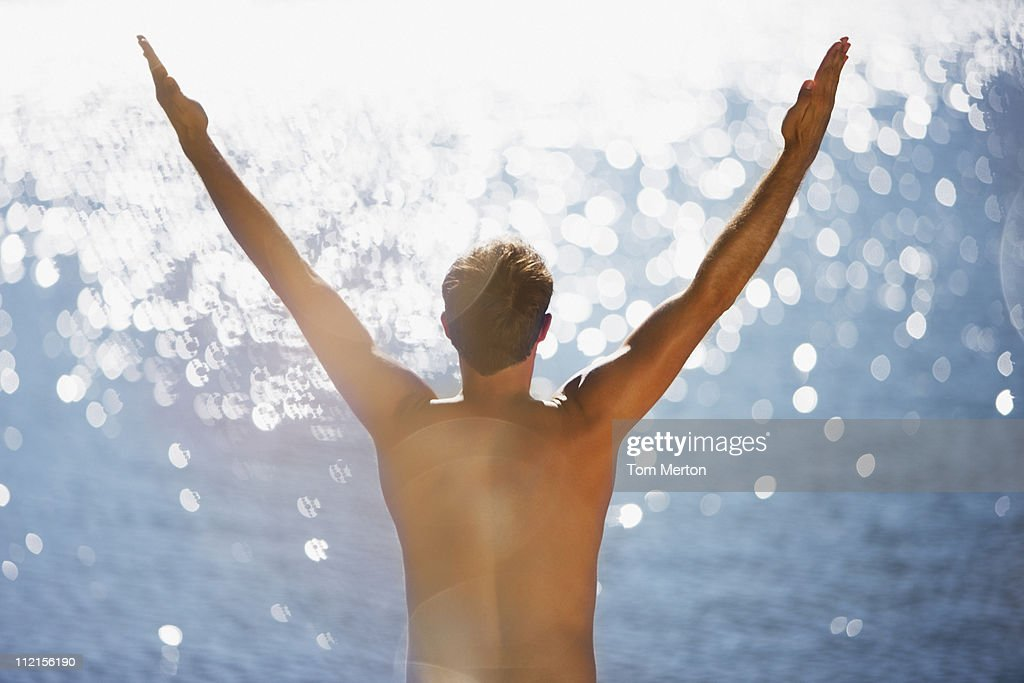 Man standing near ocean with arms raised : Stock Photo