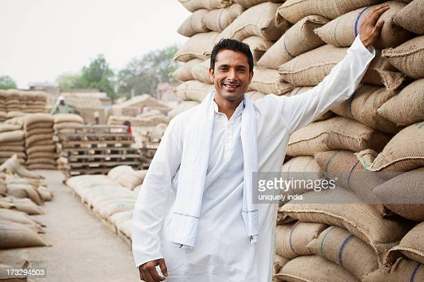 Man standing near stacks of wheat sacks in a warehouse, Anaj Mandi, Sohna, Gurgaon, Haryana, India