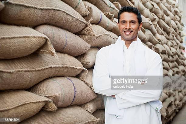 Man standing near stacks of wheat sacks in a warehouse, Anaj Mandi, Sohna, Gurgaon, Haryana, India