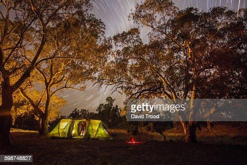 Man standing near yellow tent watching stars