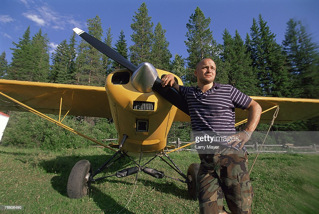 Man standing next to airplane stock photo getty images