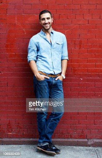 Man standing next to brick wall, portrait