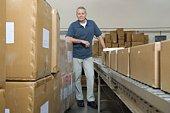 Man standing next to conveyor belt in distribution warehouse