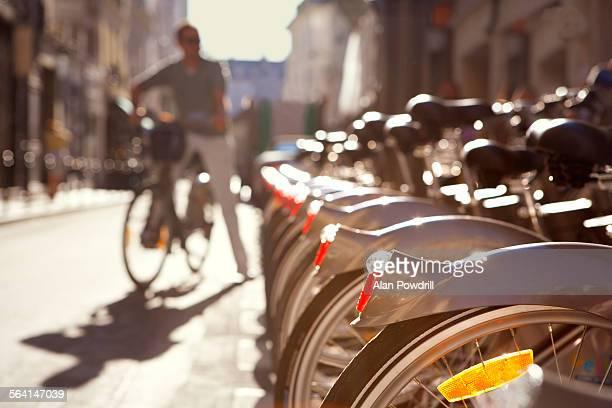 Man standing next to row of city rental bikes
