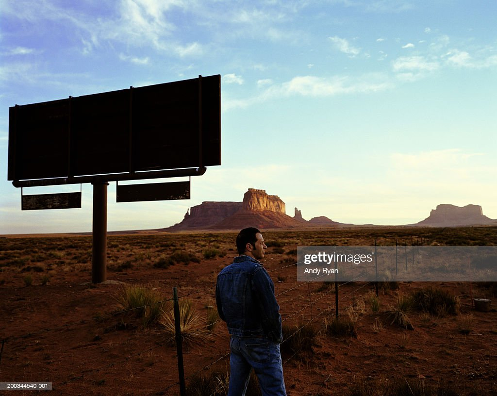 Man standing next to silhouette of billboard in desert, side view : Stock Photo