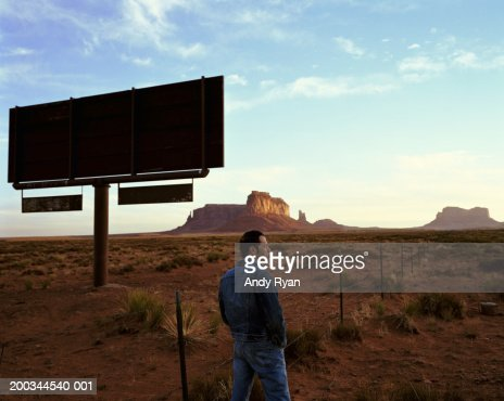 Man standing next to silhouette of billboard in desert, side view : Bildbanksbilder