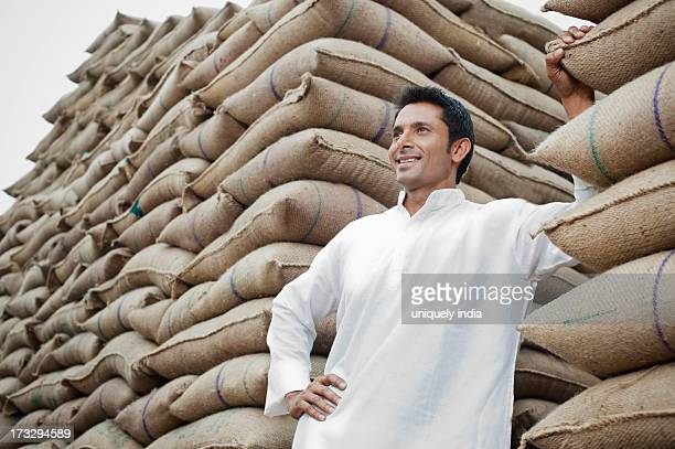 Man standing next to stack of wheat sacks, Anaj Mandi, Sohna, Gurgaon, Haryana, India