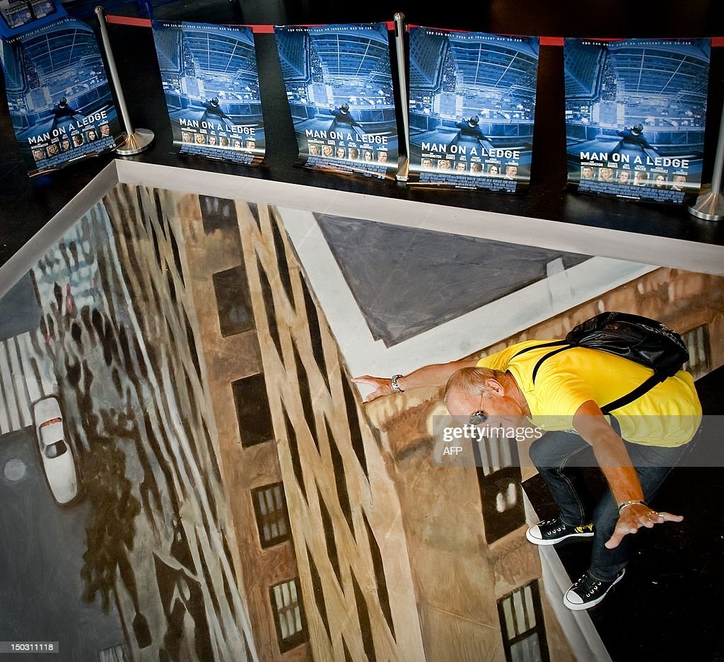 A man standing on a 3D art picture in DVD shop 'Fame' in Amsterdam, on August15, 2012. The artwork was placed to mark the Dutch DVD release of the blockbuster movie 'Man on a Ledge'. AFP PHOTO/ANP ROBIN VAN LONKHUIJSEN netherlands out