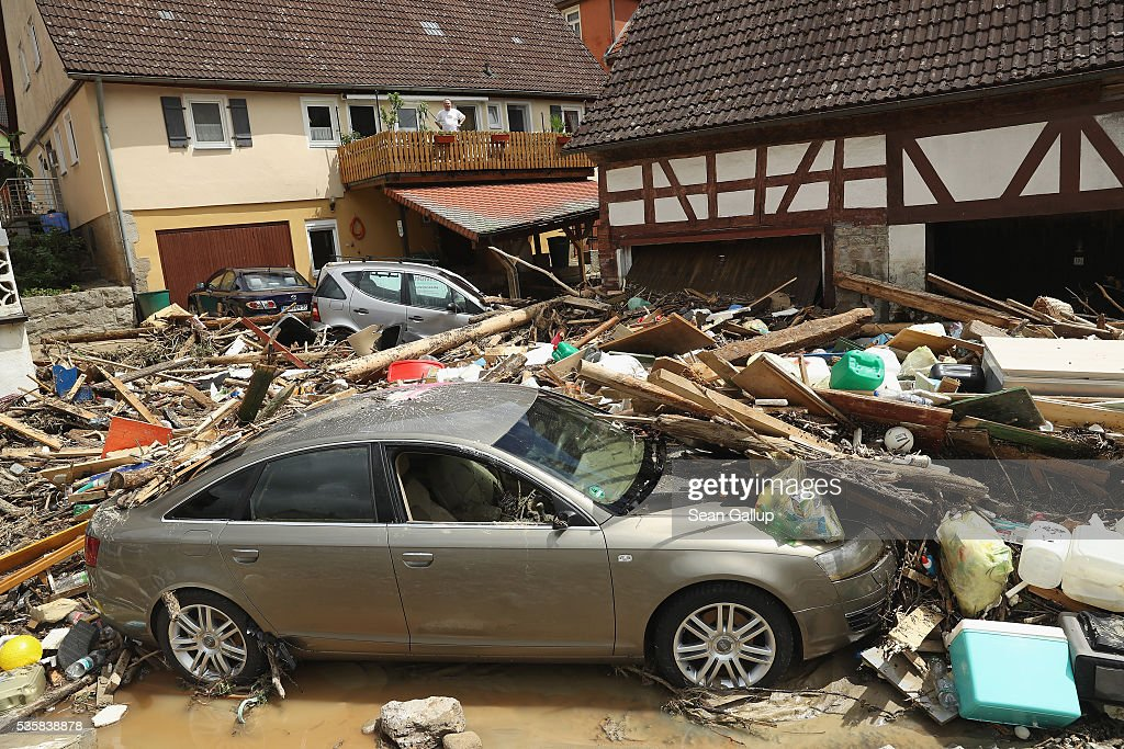 A man standing on a balcony looks at cars smashed among debris following a furious flash flood the night before on May 30, 2016 in Braunsbach, Germany. The flood tore through Braunsbach, crushing cars, ripping corners of houses and flooding homes during a storm that hit southwestern Germany. Miraculously no one in Braunsbach was killed, though three people died as a result of the storm in other parts of the country.