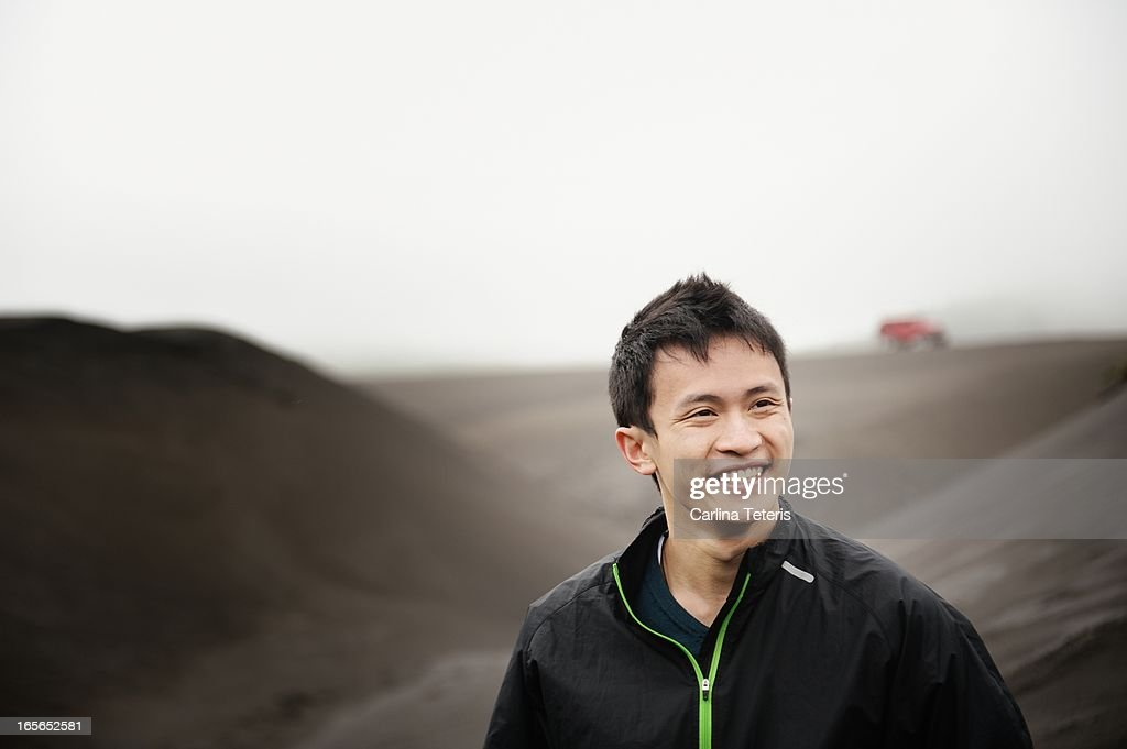 A man standing on a black sand dune