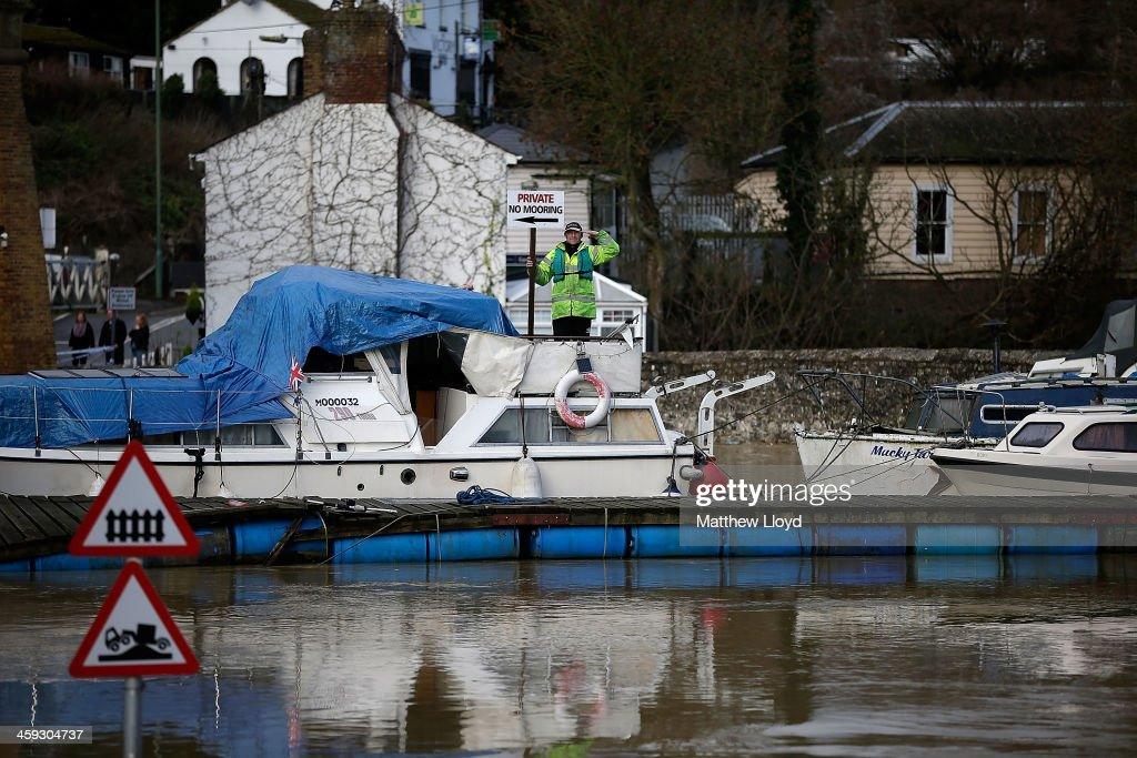 A man standing on a boat lifted high by floodwater gestures on December 25, 2013 in Tovil, United Kingdom. Christmas plans have been badly affected for thousands of people after storms across the UK have resulted in flooding, power cuts and significant problems with transport infrastructure.