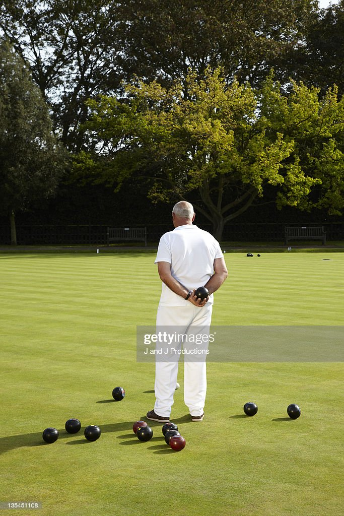 Man standing on a bowling green from behind