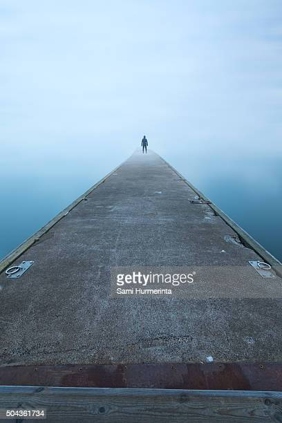 Man standing on a foggy pier