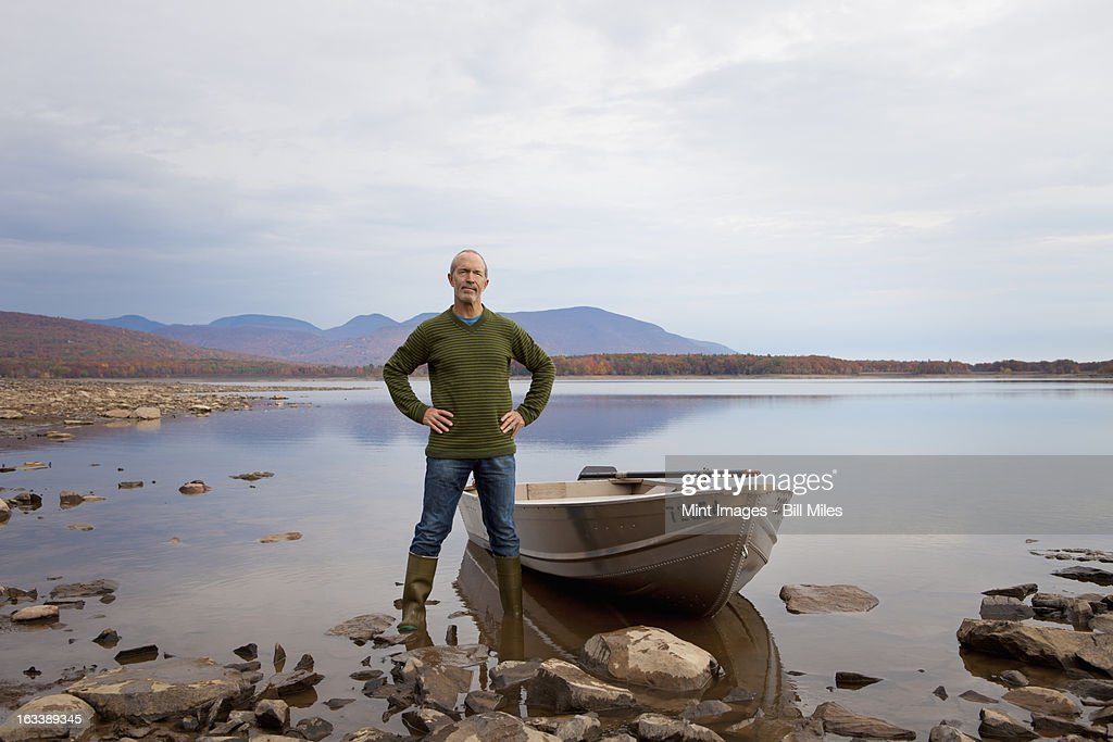 A man standing on a lake shore beside a small rowing boat. : Stock Photo