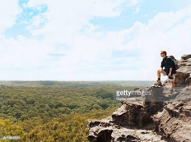 Man Standing on a Mountain Summit Holding a Pair of Binoculars