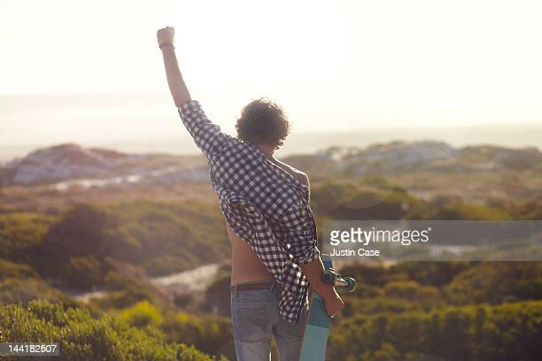Man standing on a peak looking out over a beach