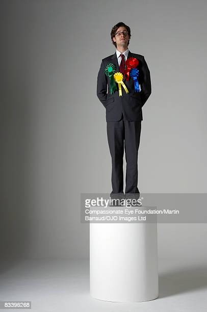 Man standing on a pedestal, wearing many ribbons