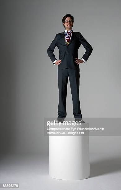 Man standing on a pedestal, wearing two medals