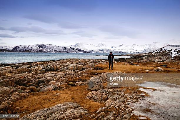 Man standing on a rocky beach in winter, Norway