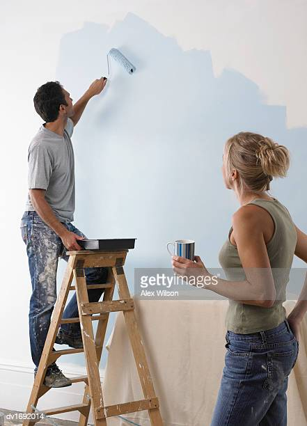 Man Standing on a Step Ladder Using a Paint Roller to Paint a Wall Blue, with a Woman Watching on