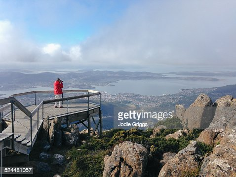Man standing on a viewing platform taking photo's