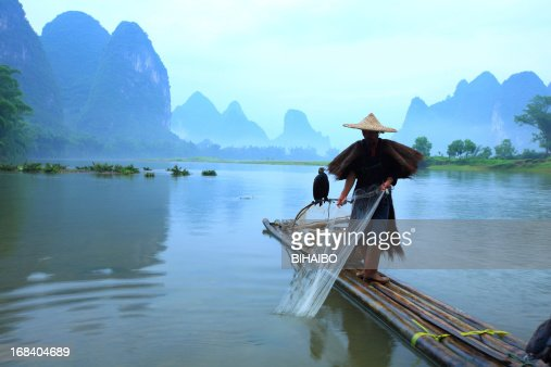 Man standing on bamboo planks with fishing net