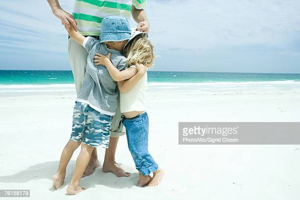'Man standing on beach with son and daughter hugging his legs, waist down'