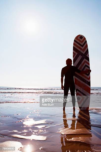 Man standing on beach with surfboard.